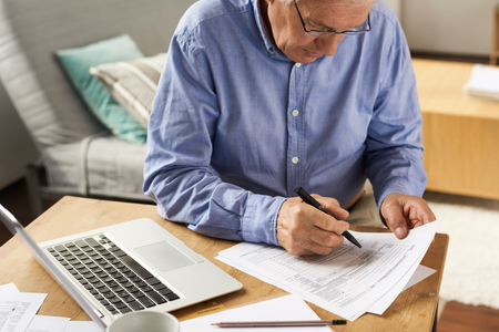 Senior Man Filling Application Form at Home Standard-Bild