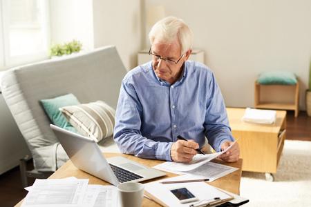 Senior Man Filing Tax Report at Home