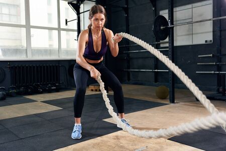 Determined  Woman Training with Battle Ropes