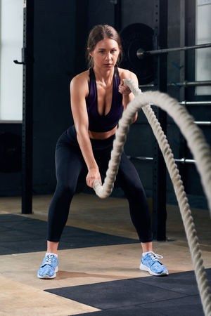 Young Woman Training with Battle Ropes  in Gym