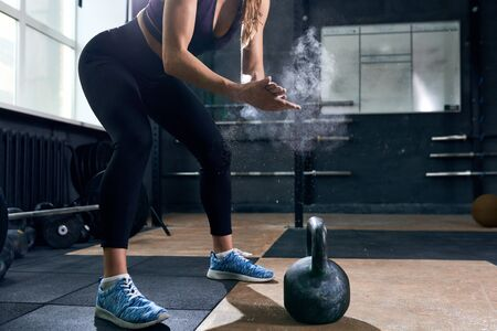 Strong Woman Lifting Kettlebells in  Gym