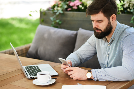 Bearded Businessman using Smartphone in Cafe Outdoors