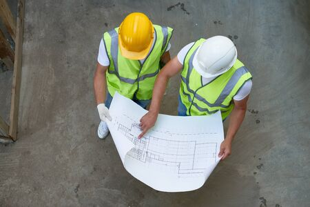 Top View of Builders Holding Blueprints