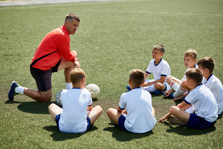 Coach Instructing Junior Football Team Stock Photo