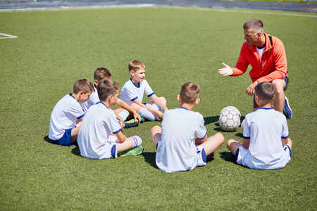 Coach Instructing  Football Team in Field