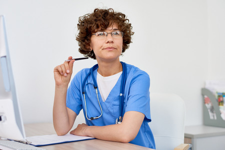 Thinking Female Doctor at Desk in office Stockfoto