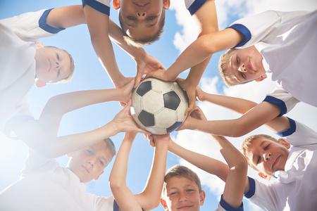 in low spirits: Happy Junior Football Team Holding Ball
