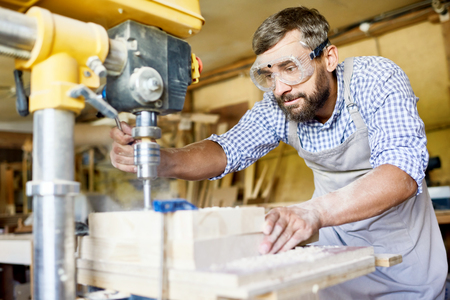 Handsome bearded carpenter wearing safety goggles and apron using drill press machine in order to make holes in wooden plank, interior of spacious workshop on background Stok Fotoğraf