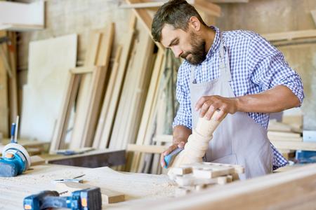 Zekere gebaarde timmerman in gecontroleerde overhemd en schort die houten detail met schuurpapier, binnenlands van slordige workshop op achtergrond oppoetsen Stockfoto