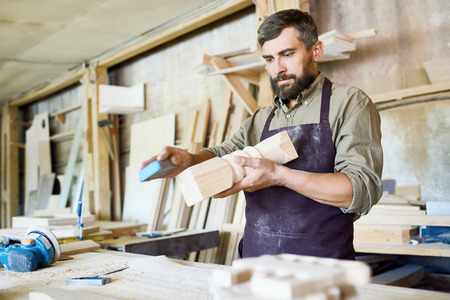 Knappe gebaarde vakman die schuurpapier gebruiken om verf van houten detail, binnenland van ruime workshop op achtergrond te verwijderen Stockfoto