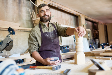 Waist-up portrait of handsome bearded carpenter looking at camera with toothy smile while distracted from polishing wooden detail with sandpaper, interior of workshop on background