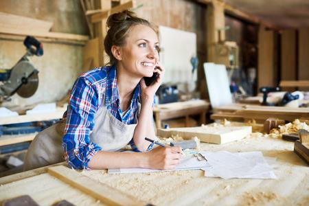 Vrolijke jonge timmerman die ordedetails bespreken met haar klant op smartphone en noodzakelijke nota's, binnenlands van ruime workshop over achtergrond nemen Stockfoto