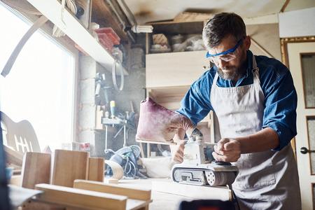 Confiado barbero carpintero vistiendo delantal y gafas de seguridad que trabajan con la lijadora de cinturón, interior de confuso taller sobre fondo