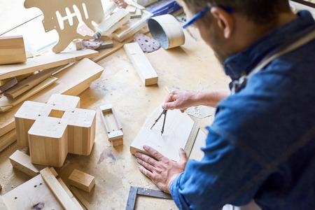 나무 판자에 동그라미를 그리기 위해 나침반을 사용하는 숙련 된 목수의 어깨 너머로 톱밥으로 덮인 지저분한 테이블
