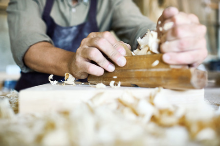 Close-up shot of unrecognizable craftsman using jointer plane, shavings on foreground