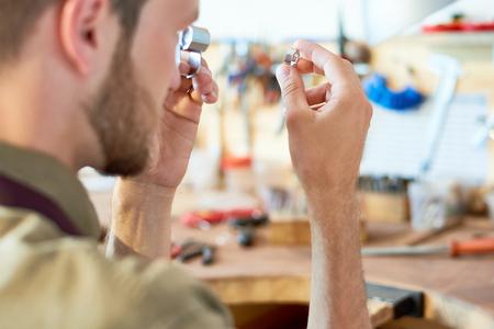 工房の虫眼鏡を通してリングを検査する宝石商の肖像