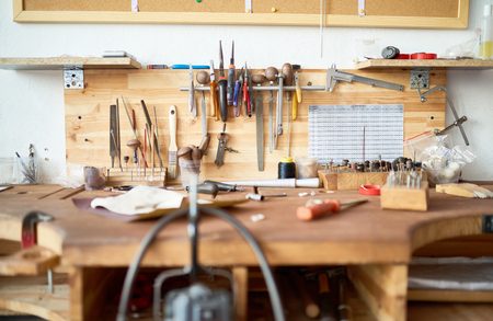 Background image of wooden workstation table in  workshop with tools for woodwork and metalwork on it Banco de Imagens