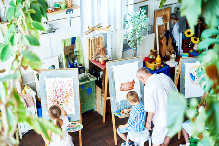 High angle view of working process at spacious art studio: creative boys and girls focused on drawing while their experienced teacher offering advice