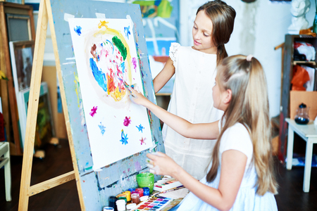 Pretty little girl standing at easel and drawing with fingers while her best friend observing her actions with interest, interior of spacious art studio on background