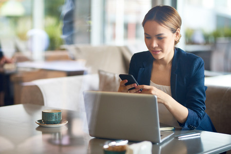 Attractive Asian entrepreneur texting with friend on smartphone while distracted from work, interior of spacious cafe on background, view through panoramic window