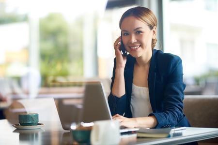 Lächelnder junger Büroangestellter, der Kamera bei der Unterhaltung mit ihrem Kollegen auf Smartphone, Innenraum des modernen Kaffeehauses auf Hintergrund, Ansicht durch panoramisches Fenster betrachtet Standard-Bild - 85559867