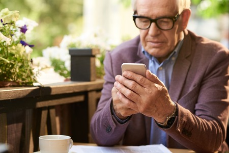 Portrait of modern senior man using smartphone in outdoor cafe, typing text messages Stock Photo