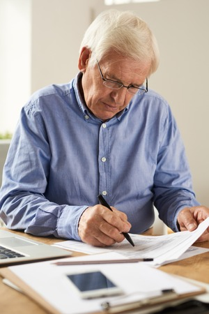 Portrait of modern senior man filling tax report or application form at home sitting at table with laptop Stock fotó