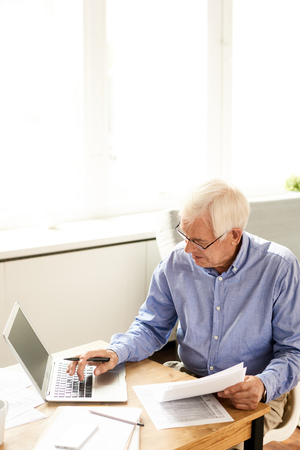 High angle portrait of modern senior man filling in application while working with laptop at home
