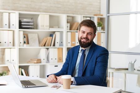 Portrait of successful  bearded businessman smiling cheerfully  while working with laptop  in modern office Фото со стока