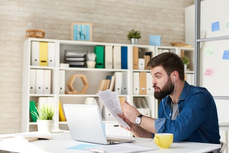 Portrait of agitated bearded man in casual wear using video call while working with laptop in modern office, discussing documentation via internet Stock Photo