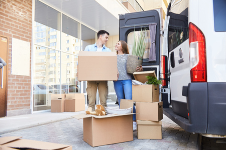 Portrait of happy young couple posing with cardboard boxes standing next to moving van outdoors