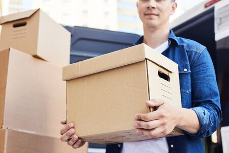 Mid-section portrait of young man holding cardboard box while unloading moving van outdoors Reklamní fotografie - 85560612