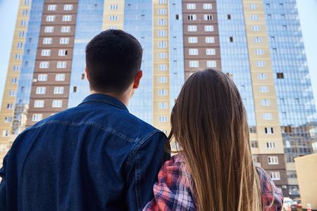 Back view portrait of young couple embracing looking at new apartment building, before moving in