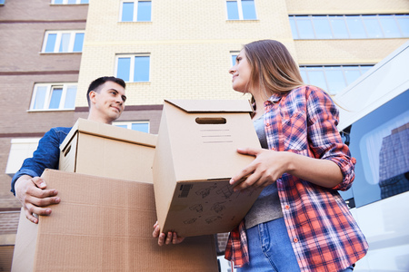 Low angle portrait of happy couple holding cardboard boxes while moving into new home, outdoors