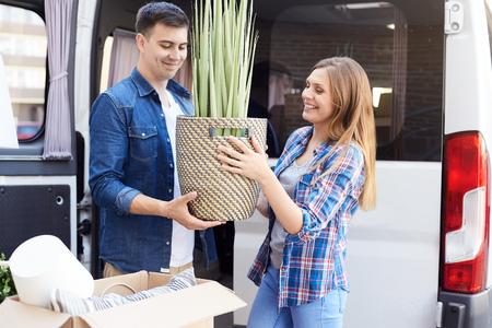 Portrait of happy young couple moving in new home, holding house plant and smiling outdoors Stok Fotoğraf