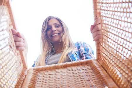 moving box: Portrait of happy young woman looking into wicker basket and smiling, shot from inside the box Stock Photo