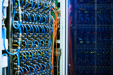 Background image of supercomputer server cabinets with wires in research center
