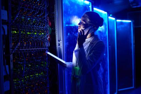 Portrait de la belle scientifique travaillant avec supercalculateur dans la lumière du néon, parlant par téléphone et tenant une tablette numérique