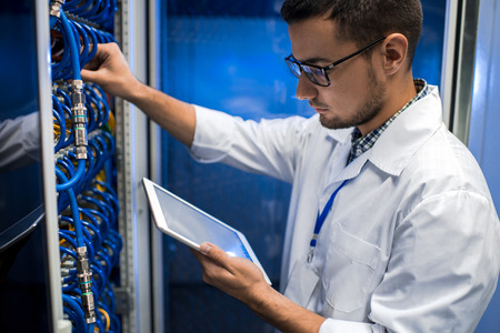Portrait of young man wearing lab coat working with supercomputer connecting blade server cables and  checking data on digital tablet