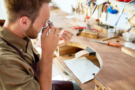 ワーク ショップで虫眼鏡を通してリングを見て若い宝石商の肖像画 写真素材
