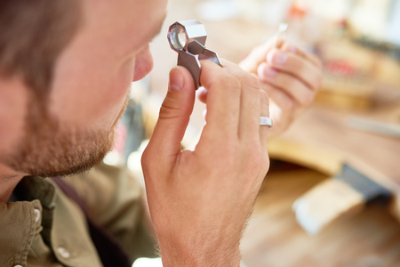 Closeup portrait of jeweler inspecting ring through magnifying glass in workshop