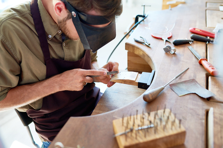 High angle portrait of jeweler making ring in workshop, forming and polishing it with tools