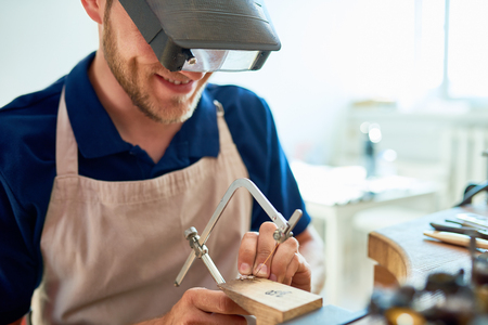 Portrait of smiling young  jeweler making ring decoration in workshop, forming it on work station with different tools Stock Photo