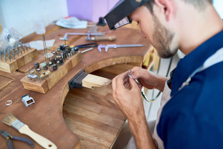 Portrait of craftsman making jewelry in workshop, forming and polishing it on work station with different tools Stock Photo