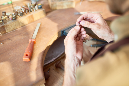 Closeup of jewelers hands making silver ring decoration in workshop, forming it on work station with different tools Фото со стока