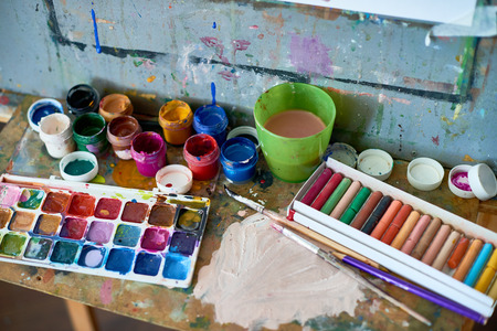 Background image of messy art supplies set on shelf of artists easel: watercolor and gouache paints,  pastel chalk next to used paintbrushes and cup of water