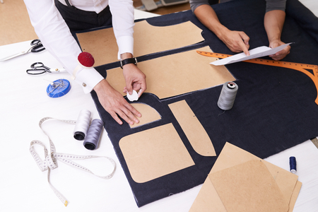 High angle view of unrecognizable designer making pattern on fabric with tailors chalk while making male jacket, his colleague standing next to him and pointing at sheet of paper