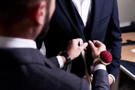 Over shoulder view of bearded fashion designer fitting bespoke suit to model, close-up shot Foto de archivo