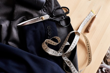 Close-up shot of two classical jackets, scissors, measuring tape and awl lying on working table at sewing atelier