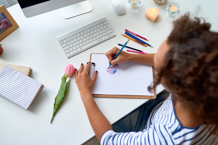 High angle portrait of young woman drawing sketch of beautiful tulip flower at desk in modern apartment